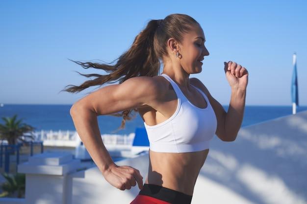 Pozytywna kobieta sprawny na letnim porannym joggingu na nabrzeżu na tle zbliżenia wybrzeża morskiego