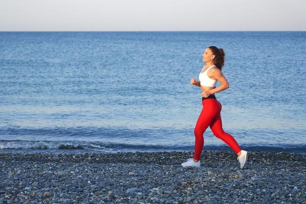 Pozytywna kobieta sprawny na letnim porannym joggingu na plaży w czerwonych legginsach na tle wybrzeża morskiego