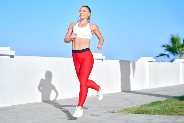 Pozytywna kobieta sprawny na letnim porannym joggingu na plaży w czerwonych leginsach na tle wybrzeża morskiego