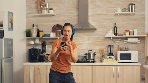 Pozytywna kobieta tańczy rano słuchając muzyki na słuchawkach. energiczna, pozytywna, szczęśliwa, zabawna i urocza gospodyni tańcząca samotnie w domu. rozrywka i wypoczynek samemu w domu