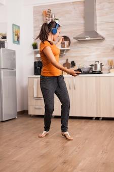 Pozytywna kobieta tańczy rano słuchając muzyki na słuchawkach