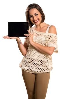 Pozytywna kobieta trzyma tabletkę.