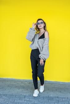 Pozytywna kobieta ubrana w ciepły szary sweter z dzianiny zimowej na białym tle na żółtej ścianie. koncepcja piękna i emocji