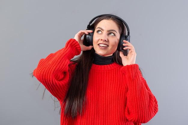 Pozytywna kobieta ubrana w czerwony sweter słucha muzyki w słuchawkach, na szarym tle