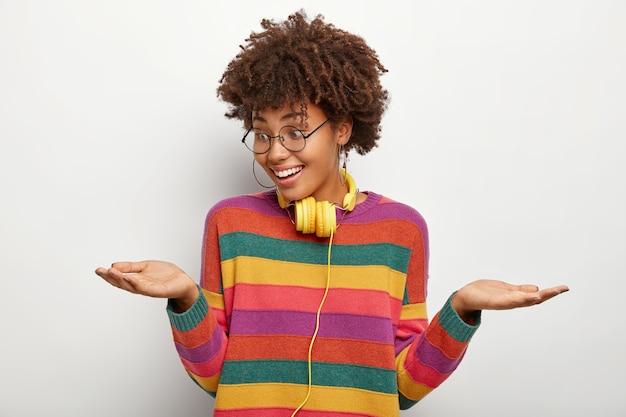 Pozytywna kobieta unosi dłonie, trzyma dwa niewidoczne przedmioty, podejmuje decyzję między dobrymi propozycjami, nosi okulary optyczne i sweter w paski