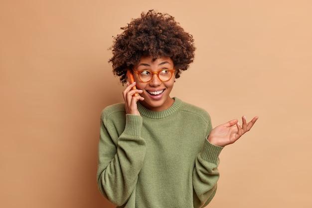 Pozytywna kobieta uśmiecha się szeroko i patrzy na bok, trzyma rękę uniesioną do góry, radośnie prowadzi zabawną rozmowę, nosi okulary optyczne i sweter odizolowany na brązowej ścianie
