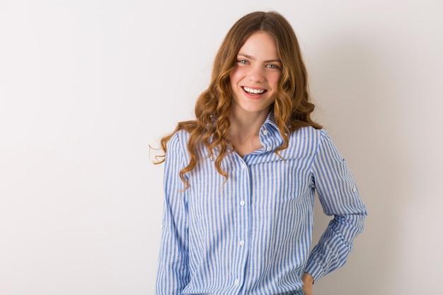 Pozytywna kobieta uśmiechnięta szczerze, młoda naturalnie wyglądająca dama w wieku studenckim w niebieskiej bawełnianej koszuli