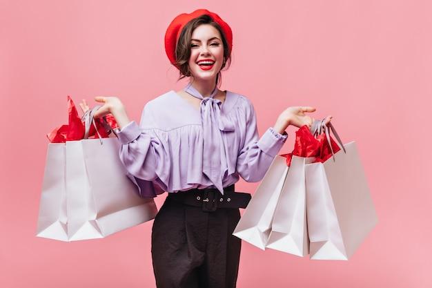 Pozytywna kobieta w czerwonym berecie i modnej bluzce uśmiecha się i trzyma torby ze sklepów odzieżowych.