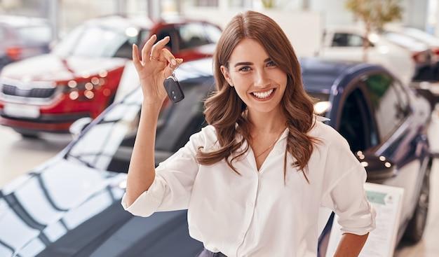 Pozytywna kobieta w inteligentnych ubraniach codziennych, uśmiechnięta do kamery i pokazująca klucze, stojąc w pobliżu nowego pojazdu w salonie