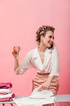 Pozytywna kobieta w jedwabnej bluzce z uśmiechem rozmawia przez telefon, prasuje ubrania i trzyma kieliszek martini