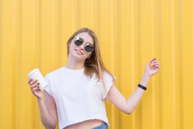 Pozytywna kobieta w okularach i białej koszulce z filiżanką kawy w dłoniach na żółtej ścianie