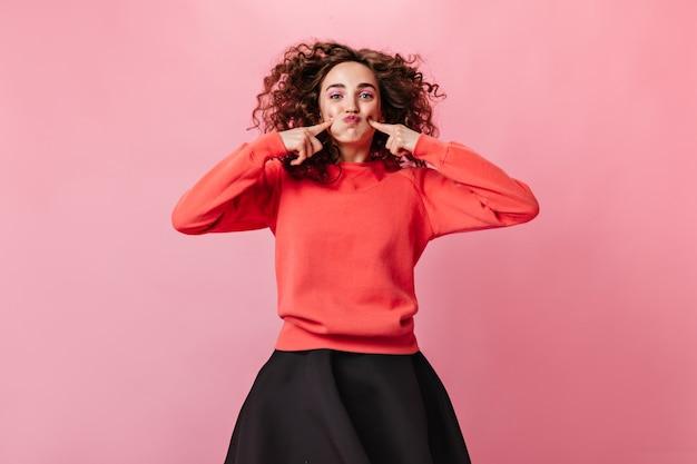Pozytywna kobieta w pomarańczowej bluzie robi śmieszną minę na różowym tle