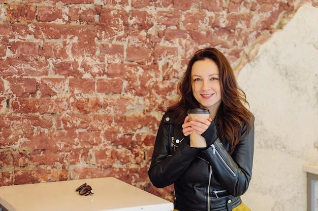 Pozytywna Kobieta W Stylowe Ubrania Pije Napój Na Wynos Siedząc Przy Stole Na Ulicy W Pobliżu Kawiarni W Ciągu Dnia Premium Zdjęcia
