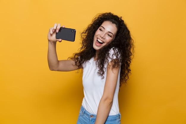 Pozytywna kobieta w wieku 20 lat z kręconymi włosami, trzymająca smartfona i robiąca zdjęcie selfie na żółto