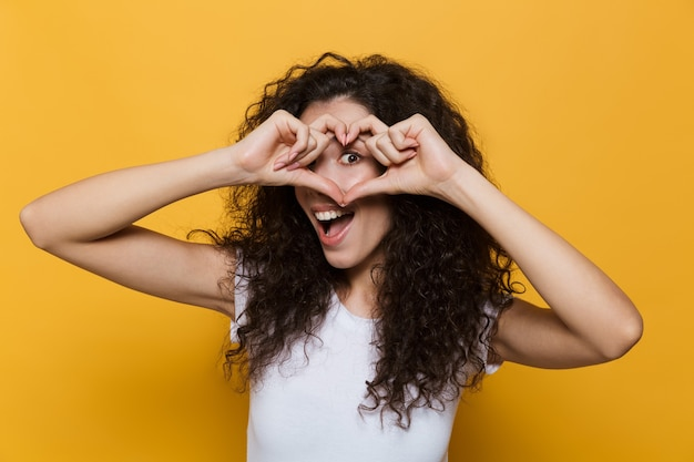 Pozytywna kobieta w wieku 20 lat z kręconymi włosami, uśmiechnięta i pokazująca kształt serca z palcami izolowanymi na żółto