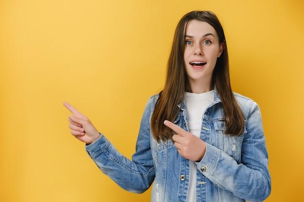 Pozytywna kobieta wskazuje obydwoma palcami wskazującymi