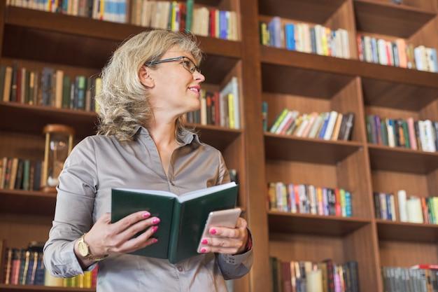 Pozytywna kobieta z biznesowym dzienniczkiem, półka na książki tło