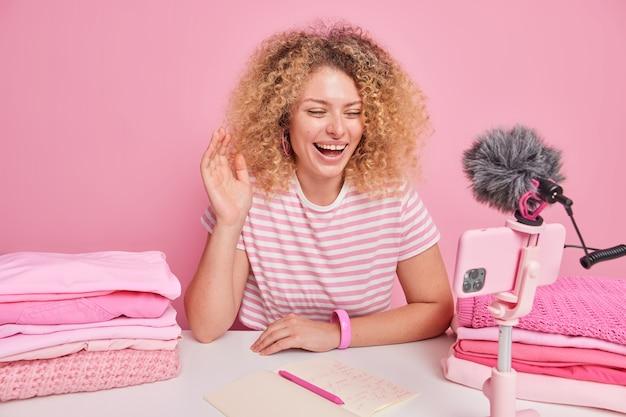Pozytywna kobieta z kręconymi włosami macha witam w aparacie