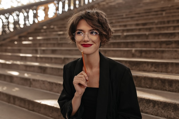 Pozytywna kobieta z krótkimi włosami i jasnymi ustami w okularach, uśmiechając się na zewnątrz. modna pani w czarnych ubraniach pozuje na schodach.