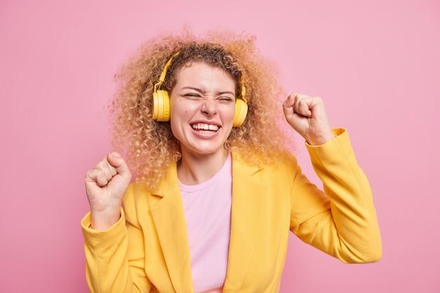 Pozytywna kobieta z naturalnymi kręconymi włosami tańczy beztrosko sprawia, że triumfalny uśmiech uśmiecha się szeroko lubi słuchać ścieżki dźwiękowej przez bezprzewodowe słuchawki