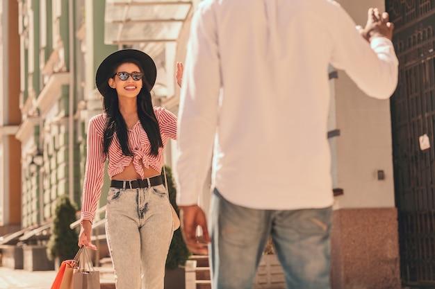 Pozytywna kobieta z torbami na zakupy witająca swojego przyjaciela na ulicy