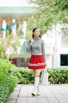 Pozytywna ładna azjatycka nastolatka spacerująca na świeżym powietrzu z papierowymi torbami po zakupach