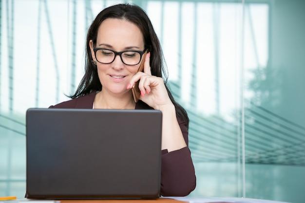 Pozytywna ładna bizneswoman w okularach rozmawia przez telefon komórkowy, pracując na komputerze w biurze, za pomocą laptopa przy stole