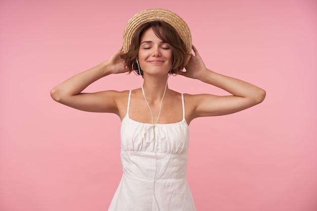 Pozytywna ładna brunetka kobieta z przypadkową fryzurą, trzymając się za ręce na słomkowym kapeluszu podczas pozowania, ciesząc się ulubionym utworem muzycznym z zamkniętymi oczami