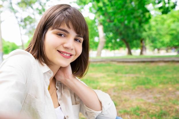 Pozytywna ładna kobieta bierze selfie fotografię i siedzi na gazonie