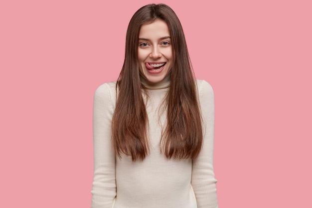 Pozytywna ładna kobieta oblizuje usta, gdy widzi coś smacznego, niedbale ubraną