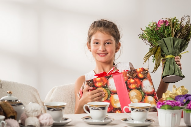Pozytywna ładna mała dziewczynka trzyma prezenta nowego roku