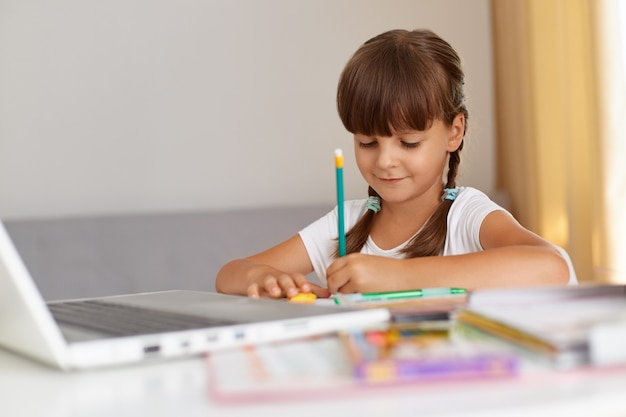 Pozytywna, ładna uczennica w swobodnym stroju, pisząca w zeszycie, mająca pozytywny nastrój, siedząca przy stole w salonie, edukacja online.
