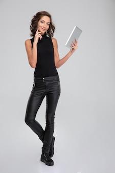 Pozytywna ładna uśmiechnięta młoda kobieta w czarnych ubraniach za pomocą tabletu