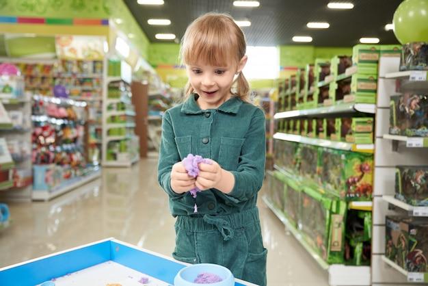 Pozytywna mała dziewczynka rzeźbi z plasteliną w zabawkarskim sklepie