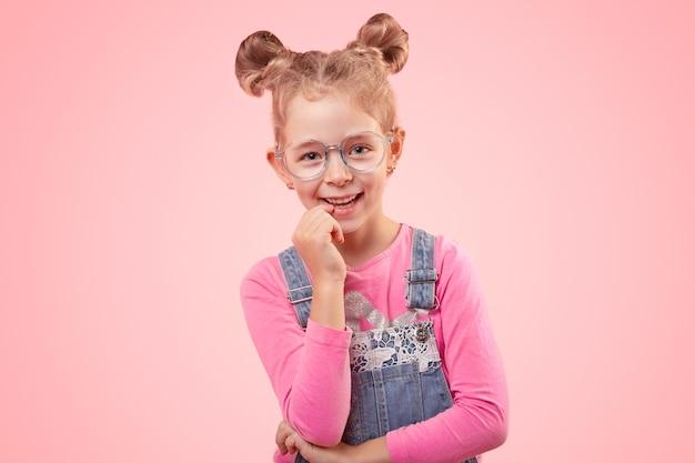 Pozytywna mała uczennica w luźnym dżinsowym kombinezonie i okularach wygląda z zainteresowaniem