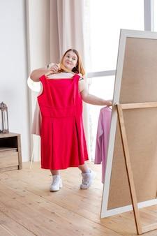 Pozytywna miła kobieta trzyma różową sukienkę, patrząc na siebie w lustrze