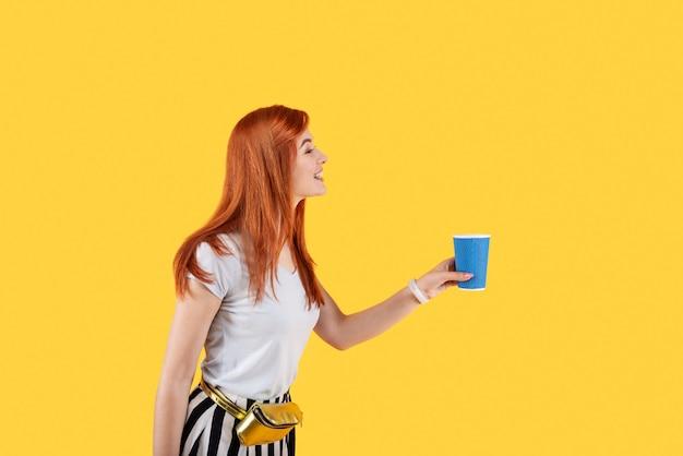 Pozytywna miła kobieta uśmiecha się trzymając filiżankę kawy