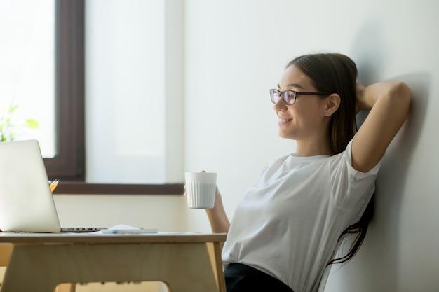Pozytywna millennial kobieta relaksuje przy pracującym miejscem w biurze