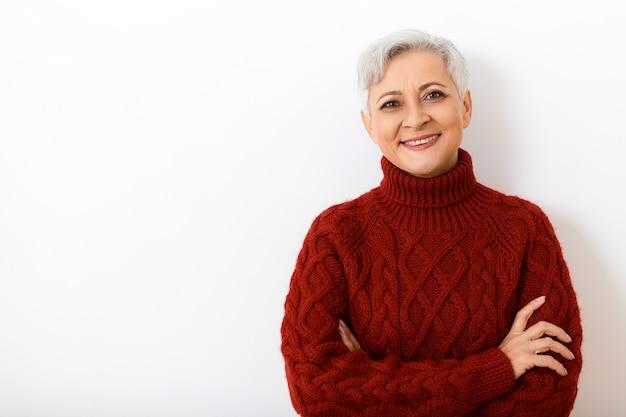 Pozytywna mimika, emocje i uczucia człowieka. przyjazny wygląd radosnej starszej kobiety w ciepłym swetrze z dzianiny o przekonanym, szczęśliwym wyglądzie, krzyżując ramiona na piersi, uśmiechając się