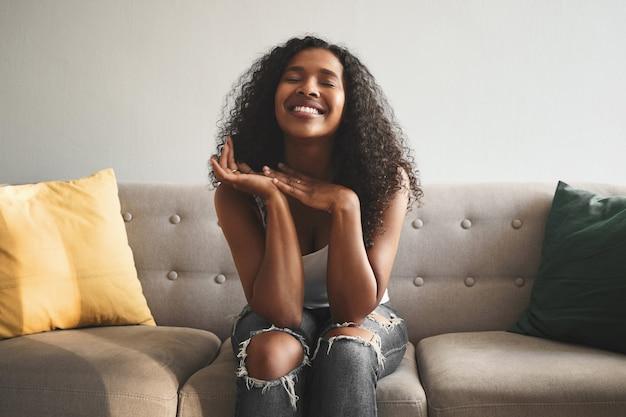 Pozytywna mimika, emocje, uczucia i reakcja człowieka. kryty ujęcie emocjonalnej szczęśliwej młodej kobiety rasy mieszanej w podartych dżinsach, zamykających oczy i szeroko uśmiechniętych, wyrażających radość