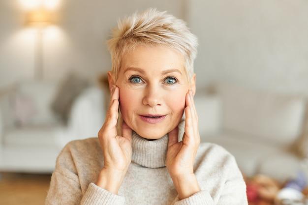 Pozytywna mimika, uczucia, emocje i reakcja człowieka. obraz emocjonalnie atrakcyjnej, dojrzałej kobiety o blond włosach i niebieskich oczach trzymającej się za ręce na twarzy, zdumionej czymś