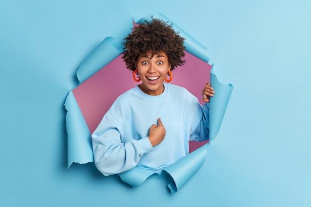 Pozytywna młoda afroamerykańska kobieta wskazuje na siebie, uśmiecha się szeroko