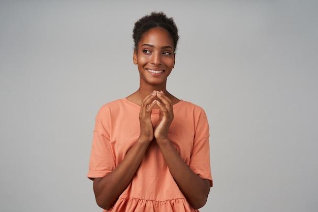 Pozytywna młoda atrakcyjna brązowowłosa, kręcona kobieta, szeroko uśmiechnięta, sprytnie patrząc na bok i trzymająca złożone ręce pod brodą, odizolowana na szarej ścianie