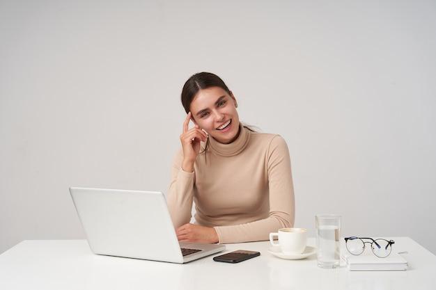 Pozytywna młoda atrakcyjna brunetka bizneswoman z fryzurą kucyka dotyka jej twarzy z podniesioną ręką, siedząc na białej ścianie i uśmiechając się radośnie