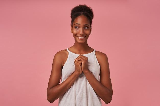 Pozytywna młoda atrakcyjna brunettened kobieta z przypadkową fryzurą, uśmiechnięta przyjemnie, patrząc na bok i składająca ręce na piersi, odizolowana na różowej ścianie