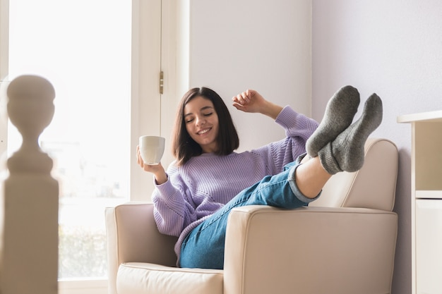 Pozytywna młoda atrakcyjna kobieta pochodzenia etnicznego w swoim pokoju trzymając filiżankę kawy i ciesząc się.
