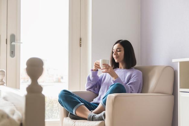 Pozytywna młoda atrakcyjna kobieta pochodzenia etnicznego w swoim pokoju, trzymając i ciesząc się filiżanką kawy.