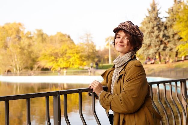 Pozytywna młoda atrakcyjna krótkowłosa brunetka kobieta oparta na żelaznej poręczy podczas pozowania nad jeziorem w parku miejskim, radośnie i uśmiechnięta