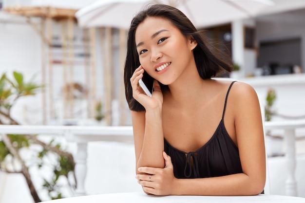 Pozytywna młoda azjatka lubi rozmawiać przez telefon komórkowy, dzieli się wrażeniami z wakacji z bliskimi, korzysta z darmowego roamingu lub ruchu telefonicznego, siada na tle kawiarni.