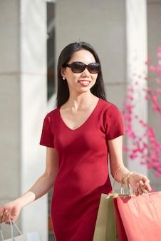 Pozytywna młoda azjatka w okularach przeciwsłonecznych i czerwonej sukience niosącej torby na zakupy podczas spaceru w centrum handlowym